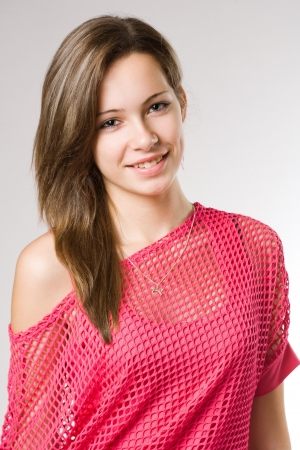 Half length portrait of a cute young student girl in pink mesh top. photo