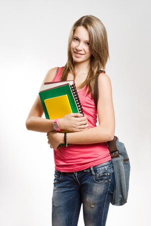 Pretty young student girl with colorful exercise books. photo