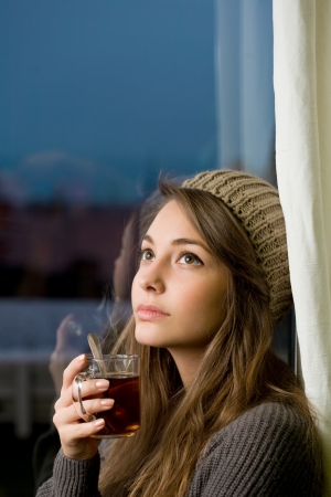 knit cap: Portrait of a pensive young brunette woman with hot tea. Stock Photo