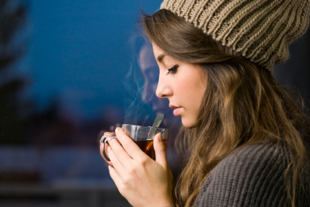 knit cap: Portrait of a dreamy young brunette with hot tea.