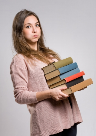 Portrait of worried looking young brunette with large pile of books. Stock Photo - 17566347