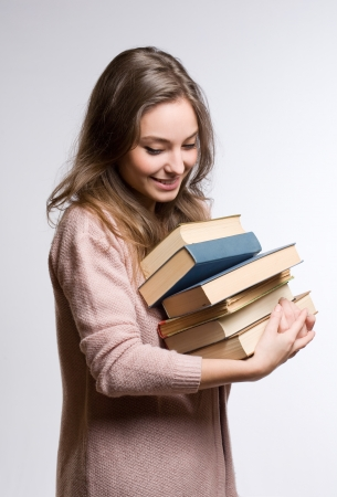 Portrait of a dreamy young brunette student holding lots of books. photo