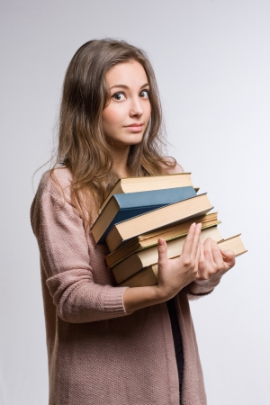 cardigan: Shocked looking young brunette woman with large pile of books.