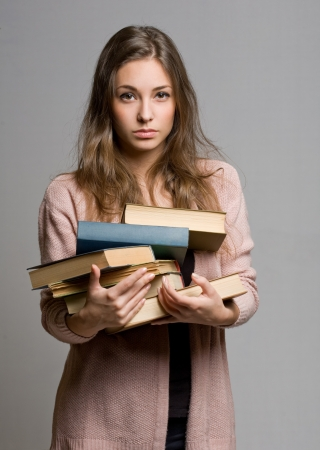 Stressed looking young student woman with lots of books. photo