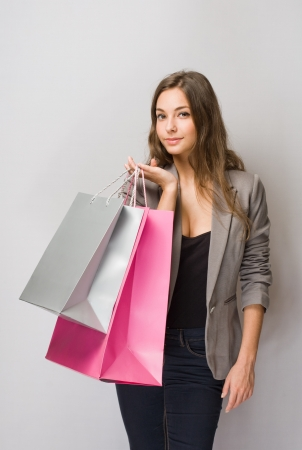 Happy young brunette shopper with colorful shopping bags. Stock Photo - 17566308