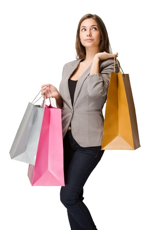 Thoughtful elegant young brunette woman with colorful shopping bags. photo
