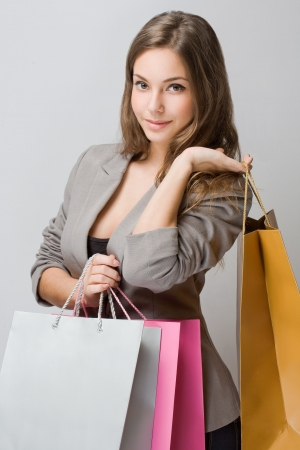 Portrait of stylish young brunette woman holding colorful shopping bags. photo