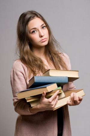 Portrait of wasted looking young student girl carrying large pile of books. Stock Photo - 17576554