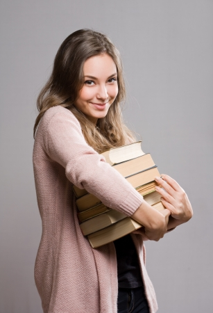 Portrait of happy student  girl hugging a pile of books. photo
