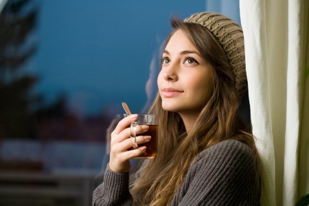 Young brunette beauty enjoying a cup of hot tea at the window. Stock Photo