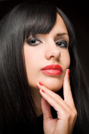 Moody portrait of beautiful brunette woman with striking red lips  photo
