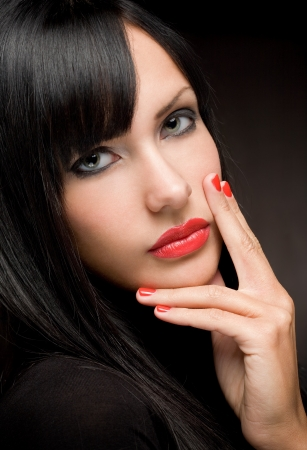 Dark beauty shot of gorgeous brunette with amazing red lips and nails  photo