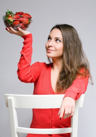 Gorgeous friendly young brunette woman with juicy strawberries  photo