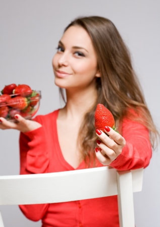 Fit young brunette woman with a bowl of juicy fresh strawberries photo