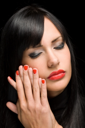 Portrait of gorgeous sensual brunette woman with bright red lips and nails. photo