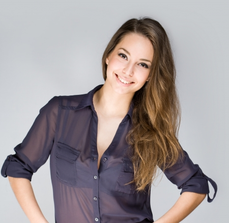 Portrait of cute fashionable young brunette woman in dark blue shirt.