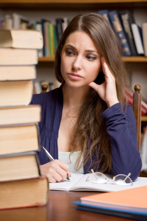 Portrait of an exhausted young brunette student woman with large pile of books  Stock Photo