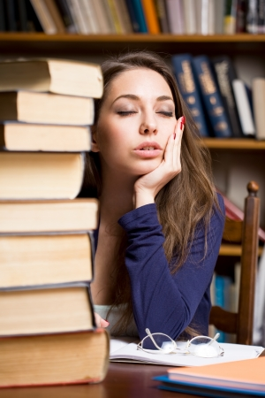 Portrait of an exhausted young brunette student woman with large pile of books  photo