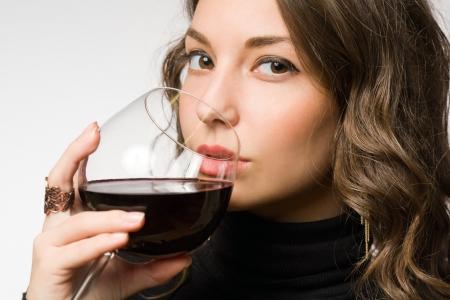 jovenes tomando alcohol: Retrato de una hermosa mujer morena joven que disfruta de vinos premium Foto de archivo