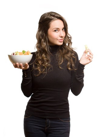 Beautiful fit young brunette with bowl of green salad. photo