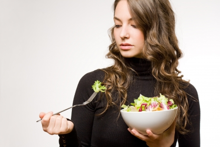 Beautiful fit young brunette with bowl of green salad.