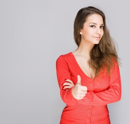 Portrait of a cute young brunette showing big thumbs up.