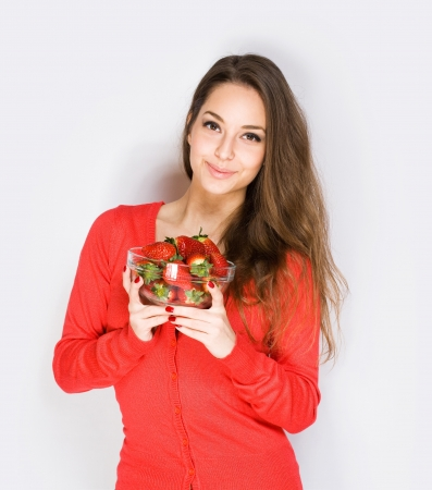 Portrait of brunette cutie with bowl of juicy strawberries. photo