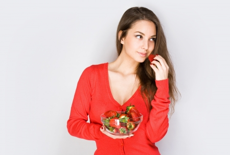 sexy asian woman: Portrait of a thoughtful brunette beauty eating strawberries. Stock Photo