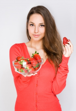Portrait of a brunette beauty offering bowl of strawberries, selective focus on the bowl. photo