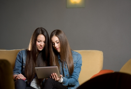 Two cute teen girls having fun with tablet computer in coffe shop. Stock Photo - 18527370