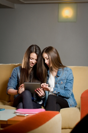 Two cute teen girls having fun with tablet computer in coffe shop. Stock Photo - 18527387