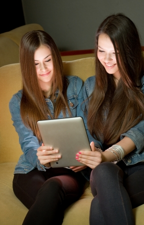 Two beautiful young girls sharing tablet computer. Stock Photo - 18527374