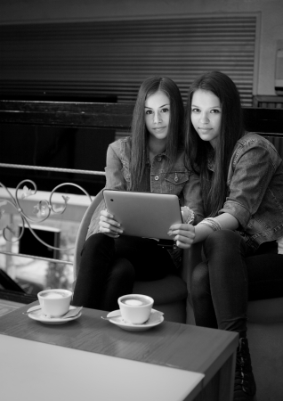 Two beautiful young girls sharing tablet computer  photo