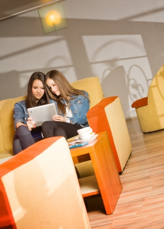Two cute teen girls having fun with tablet computer in coffe shop Stock Photo - 18514455