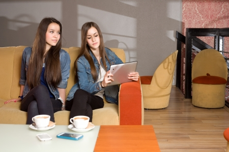Two girls loosing communication being occupied by their computers  Stock Photo - 18527377