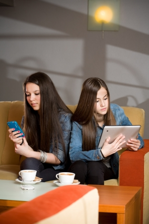 Two girls loosing communication being occupied by their computers