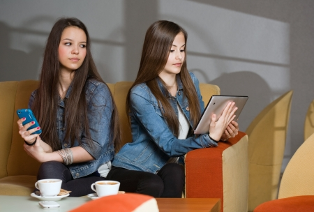 Two girls getting lost in and separated by their mobile devices Stock Photo - 18527380