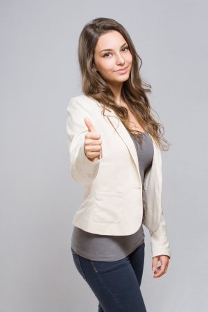 Portrait of elegant young brunette showing big thumbs up  Stock Photo