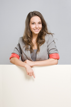 Portrait of gorgeous young businesswoman with large blank banner.