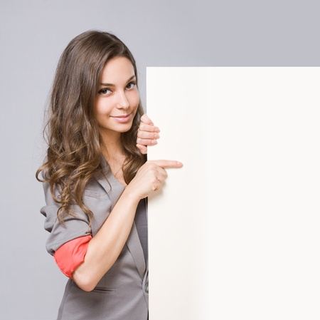 Beautiful elegant young businesswoman holding large blank white sign.