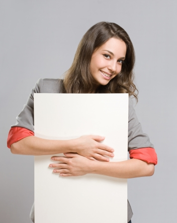 Portrait of gorgeous young businesswoman with large blank banner. photo