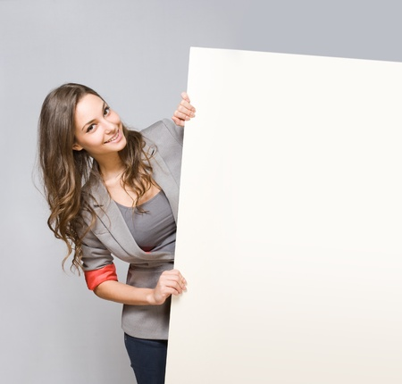 Gorgeous young brunette businesswoman holding large blank white sign  Stock Photo
