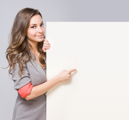 Portrait of cute young brunette woman pointing at large empty billboard  Stockfoto
