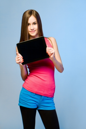 Colorful dressed expressive teen beauty holding tablet computer for copy space