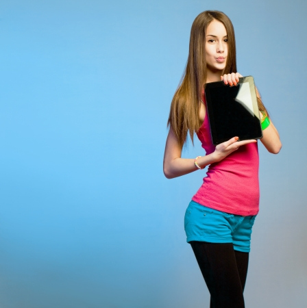 Colorful cute teen brunette with her tablet computer for copy space  photo