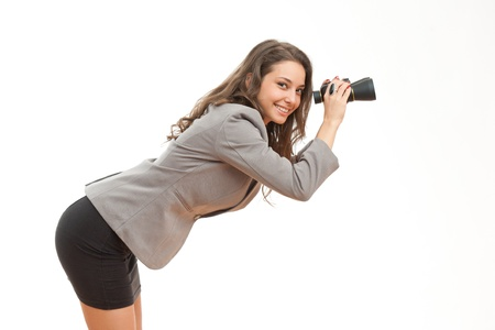 looking for work: Portrait of fashionable young businesswoman searching the horizon with binoculars  Stock Photo
