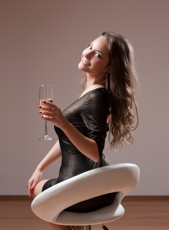 barstool: Portrait of sensual festive young brunette with glass of champagne