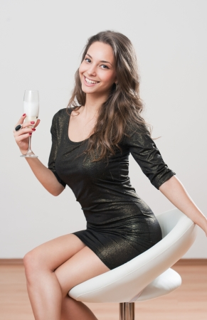 barstool: Portrait of a festive brunette beauty holding glass of champagne. Stock Photo