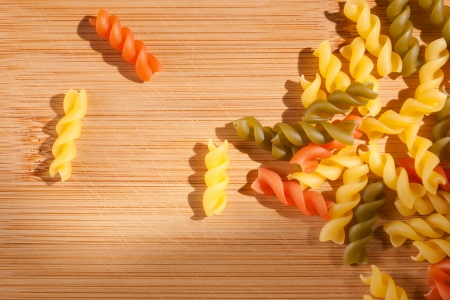 drenched: Shot of colorful italian pasta drenched in natural sunlight on cutting board  Stock Photo