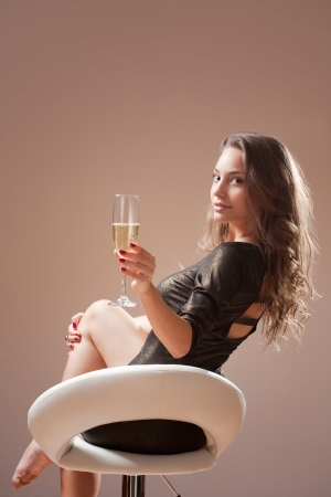 barstool: Portrait of festive brunette beauty on barstool with glass of champagne.